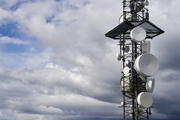 Wieże telekomunikacyjne na tle zachmurzonego nieba