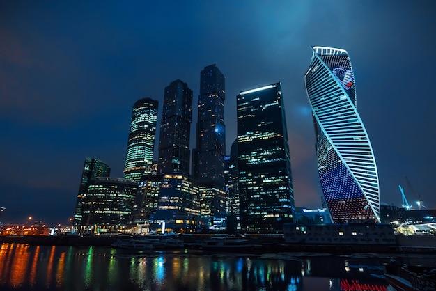 Wieże wieżowców moskwy nad rzeką z odbiciem w nocy