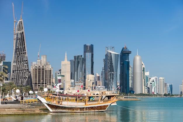 Wieżowce w centrum miasta z wodą i łodzią na pierwszym planie doha, katar.