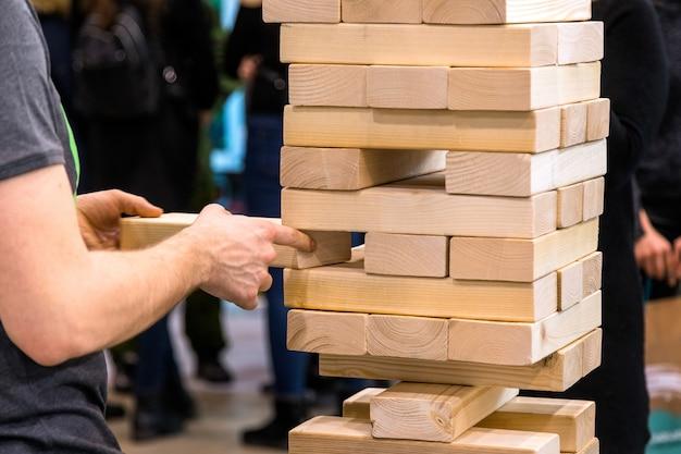 Wieżowiec, człowiek bierze drewnianą część drewnianej wieży. planowanie, ryzyko i strategia w koncepcji biznesowej