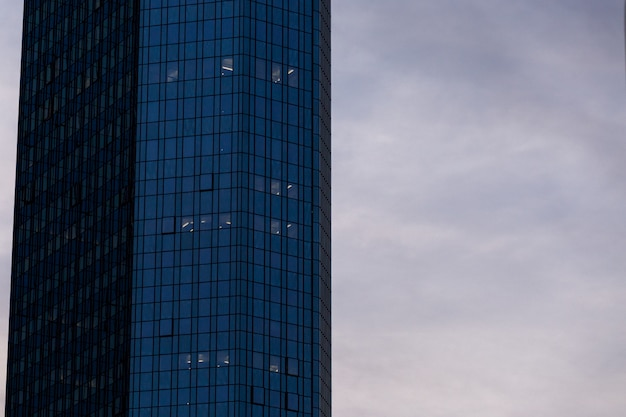 Wieżowiec w szklanej fasadzie pod chmurnym niebem w frankfurt, niemcy