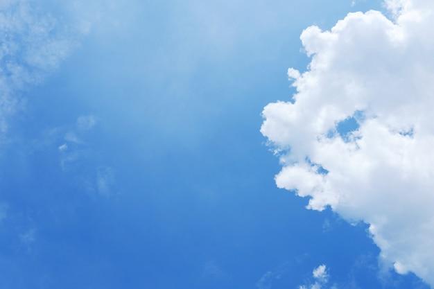 Wieżowiec z chmurami i niebieskiego nieba tłem