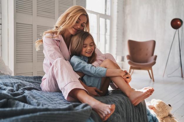 Więzy rodzinne. piękna młoda matka obejmująca córkę i uśmiechnięta siedząc na łóżku w domu