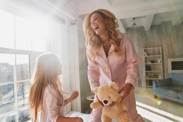 Więzy rodzinne. śliczna dziewczynka i jej młoda mama uśmiechają się podczas spędzania czasu w domu