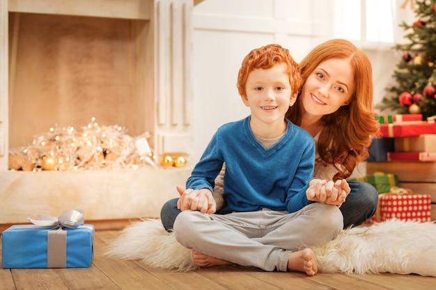 Więzy rodzinne. wesoła rodzina siedzi na podłodze, trzymając ręce razem w domu.
