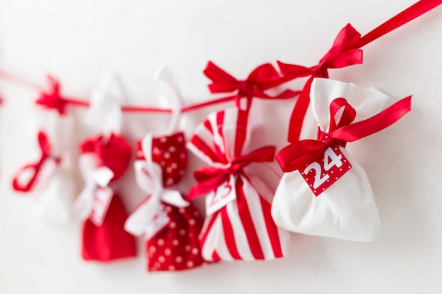 Wigilia. kalendarz adwentowy. czerwone i białe torby ze słodyczami na białym. prezenty dla dzieci