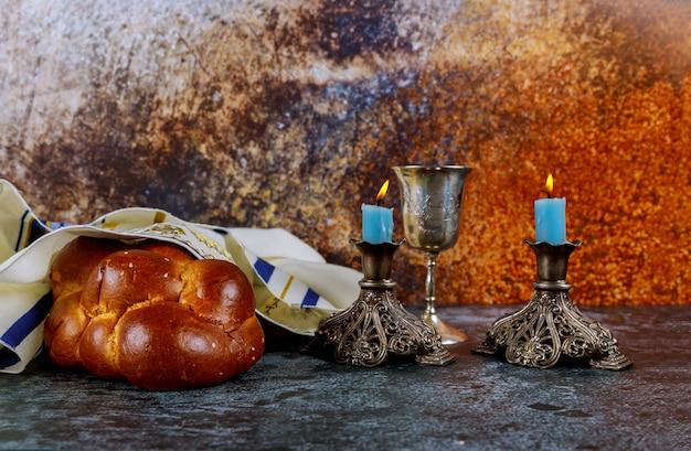 Wigilia szabatowa z chlebem chałła, świecami szabatowymi i kieliszkiem do wina kidusz.