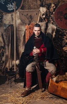 Wiking pozujący na tle starożytnego wnętrza wikingów.