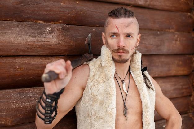 Wiking wojownik z toporem w kamizelce ze skóry w pobliżu drewnianej ściany