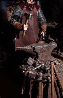 Wiking wykuwa broń i miecze w kuźni. w kuźni jest mężczyzna w stroju wojownika.