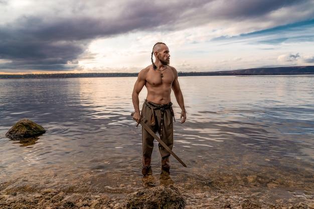 Wiking ze skórą okrytą ramionami stoi na brzegu rzeki