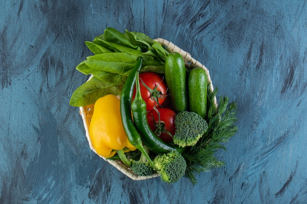 Wiklinowa miska świeżych organicznych warzyw na niebieskiej powierzchni. .