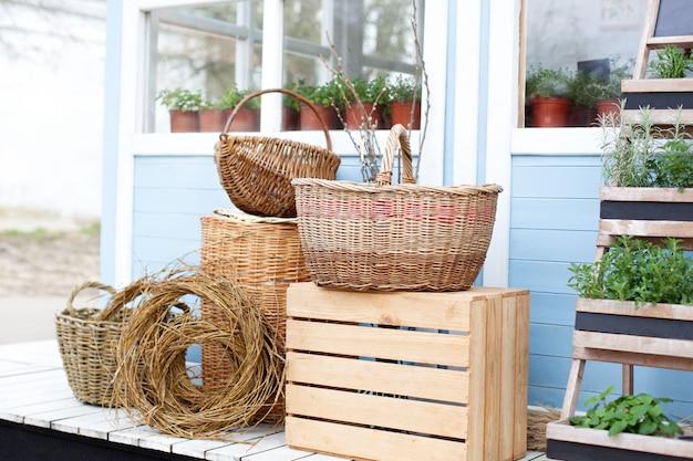 Wiklinowe kosze obok sprzętu ogrodowego przy ścianie niebieskiego wiejskiego domu. letnie wakacje sezonowe. rośliny ogrodowe w doniczkach. prace ogrodowe. domki letniskowe spring garden backyard.