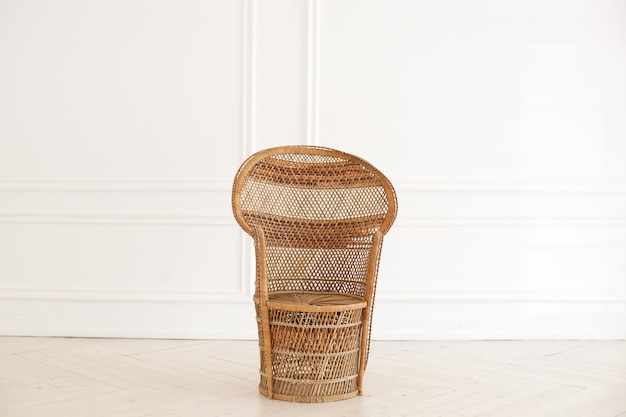 Wiklinowe krzesło pawie w przestronnym wnętrzu sypialni. rattanowy pawi fotel przy białej pustej ścianie w salonie. dom w stylu skandynawskim. wnętrze pokoju w stylu rustykalnym. meble ekologiczne, meble naturalne