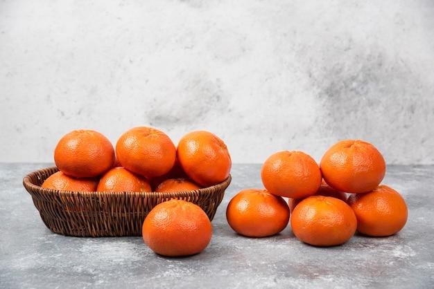 Wiklinowe pudełko pełne soczystych pomarańczowych owoców na kamiennym stole.