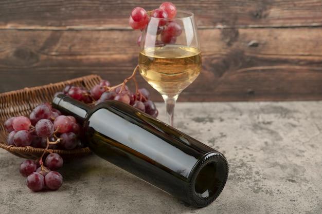 Wiklinowy kosz czerwonych winogron z lampką białego wina na marmurowym stole.