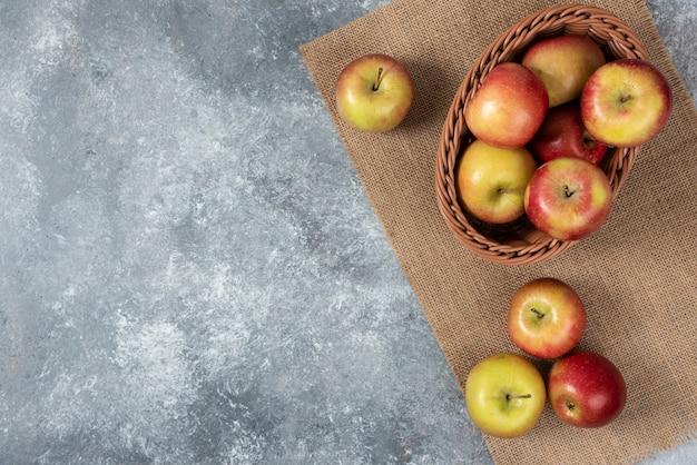 Wiklinowy kosz dojrzałych jabłek błyszczących na powierzchni marmuru.
