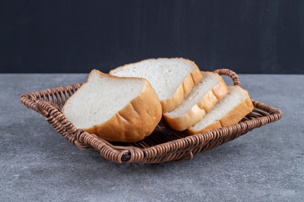 Wiklinowy kosz krojonego białego chleba umieszczony na kamiennym stole.