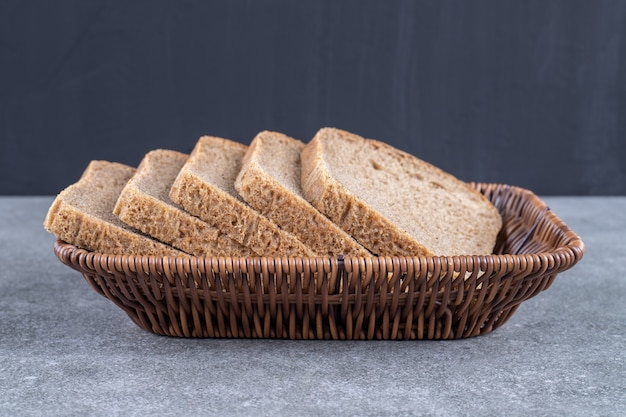 Wiklinowy kosz krojonego chleba żytniego na kamiennym stole.