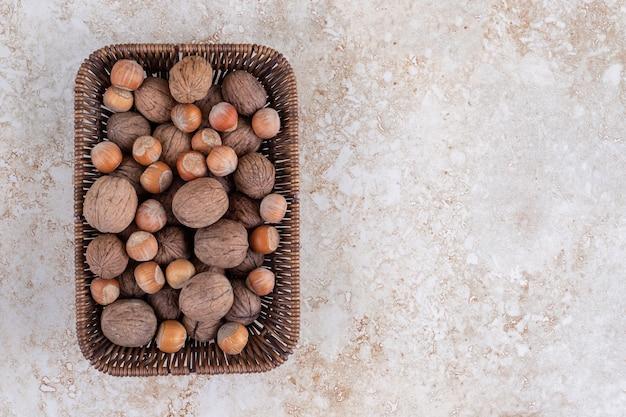 Wiklinowy kosz łuskanych orzechów włoskich i orzechów laskowych na marmurowym stole.