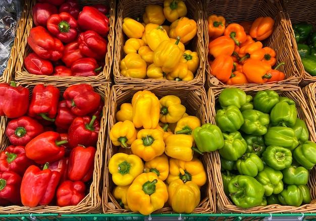 Wiklinowy kosz papryki na ladzie sklepowej. rolnicy sprzedają świeże warzywa naturalne produkty