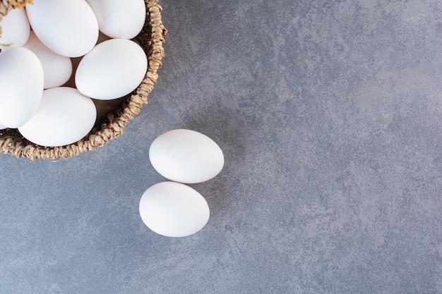 Wiklinowy kosz pełen ekologicznych jajek na kamiennym stole.