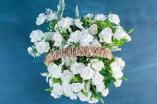 Wiklinowy kosz pełen kwiatów białych róż na niebiesko.