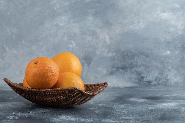 Wiklinowy kosz pełen pomarańczowych owoców.