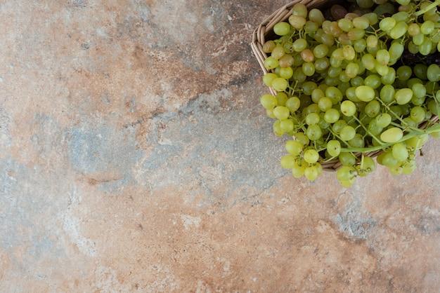 Wiklinowy kosz pełen słodkich winogron na marmurowym stole.