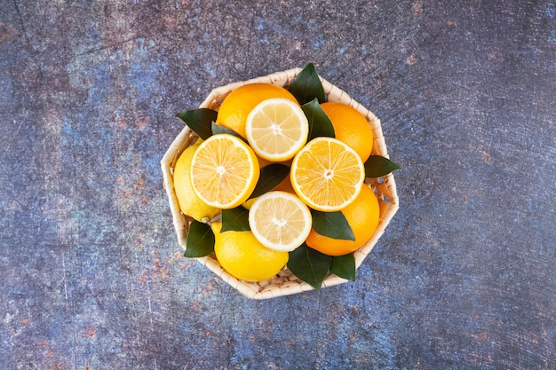 Wiklinowy kosz pełen świeżych cytryn z liśćmi na marmurze.