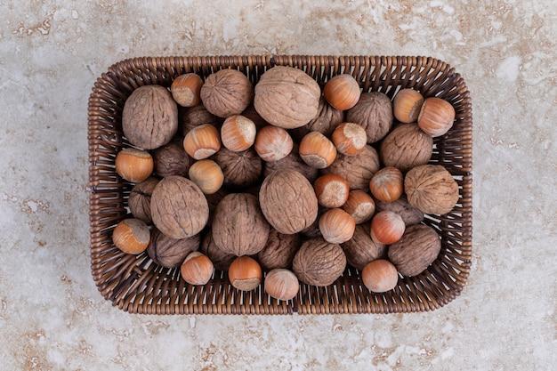 Wiklinowy kosz pełen zdrowych orzechów makadamia i orzechów włoskich umieszczony na kamiennej powierzchni.