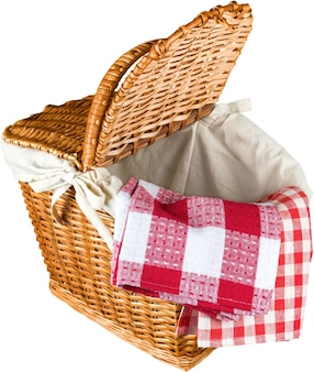 Wiklinowy kosz piknikowy z czerwoną tkaniną w kratkę na białym tle