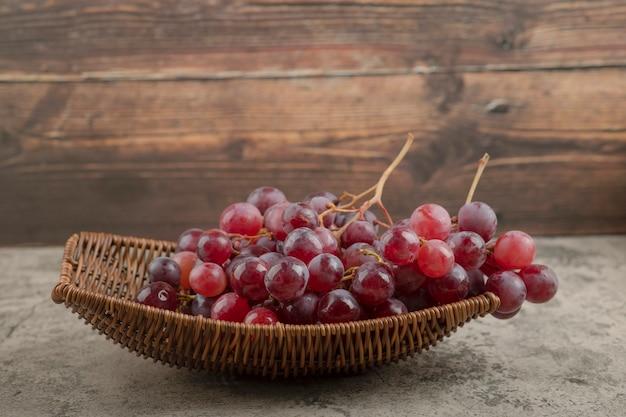 Wiklinowy kosz pysznych czerwonych winogron na marmurowym stole.