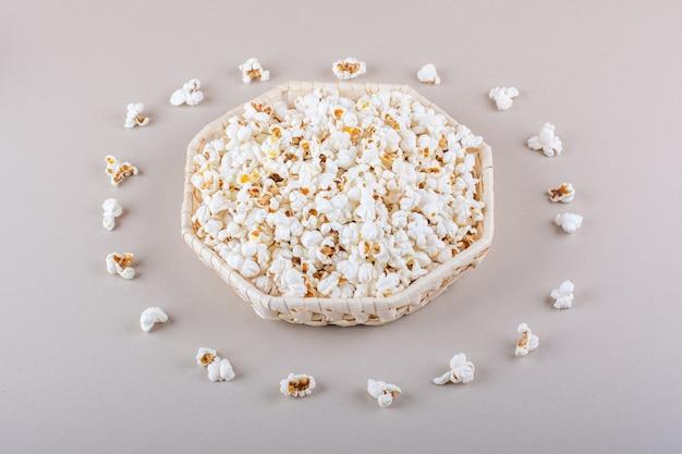 Wiklinowy kosz solonego popcornu na wieczór filmowy na białym tle. zdjęcie wysokiej jakości