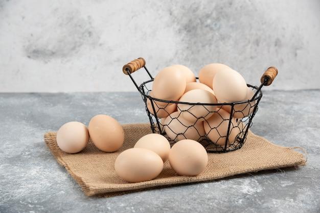 Wiklinowy kosz surowych organicznych jaj na marmurze.