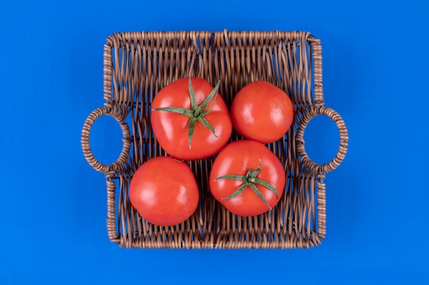 Wiklinowy kosz świeżych czerwonych pomidorów na niebieskiej powierzchni.