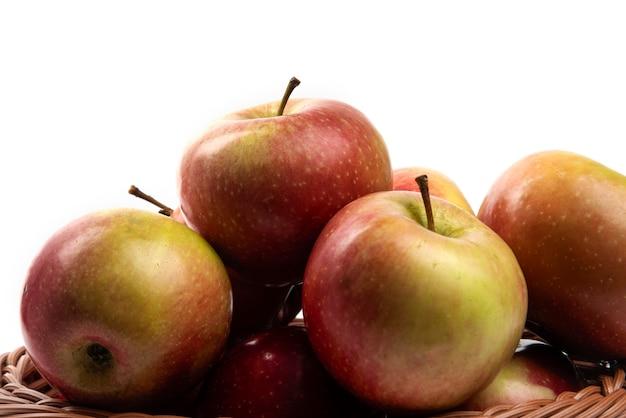 Wiklinowy kosz świeżych jabłek soczystych na białym tle.
