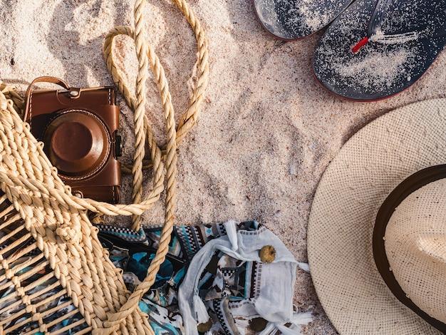 Wiklinowy kosz, vintage aparat i szal na piasku