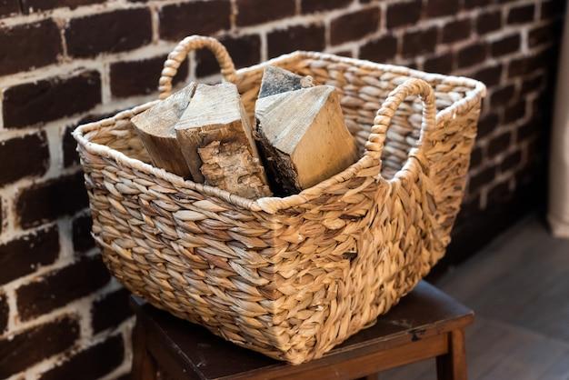 Wiklinowy kosz wykonany z papieru winorośli wypełniony drewnem opałowym. recykling, ekologiczne, naturalne materiały, ekologiczne. styl boho, rustykalny, przytulny.
