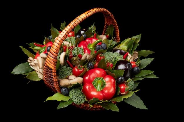 Wiklinowy kosz wypełniony różnymi świeżymi dojrzałymi warzywami na czarno