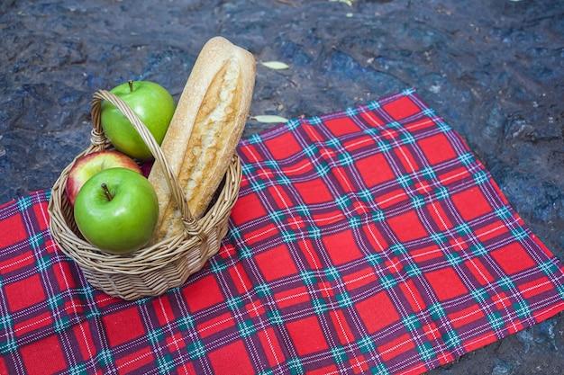 Wiklinowy kosz z bagietką, winem i jabłkami