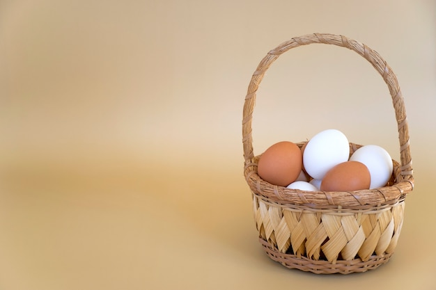Wiklinowy kosz z białymi i brązowymi jajkami na beżowym tle z miejsca na kopię. świeże jaja kurze, kompozycja wielkanocna.