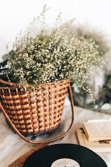 Wiklinowy kosz z bukietem suszonych kwiatów na stole.
