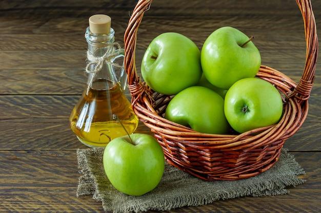 Wiklinowy kosz z dojrzałymi zielonymi jabłkami i butelką octu aplle na drewnianym tle.