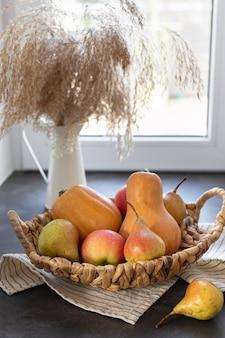 Wiklinowy kosz z dyni, jabłka gruszki i dzbanek na parapecie jesienna kompozycja na święto dziękczynienia