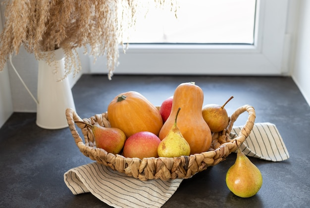 Wiklinowy kosz z dyniowymi jabłkami gruszki na ciemnym kuchennym blacie jesienna sezonowa kompozycja