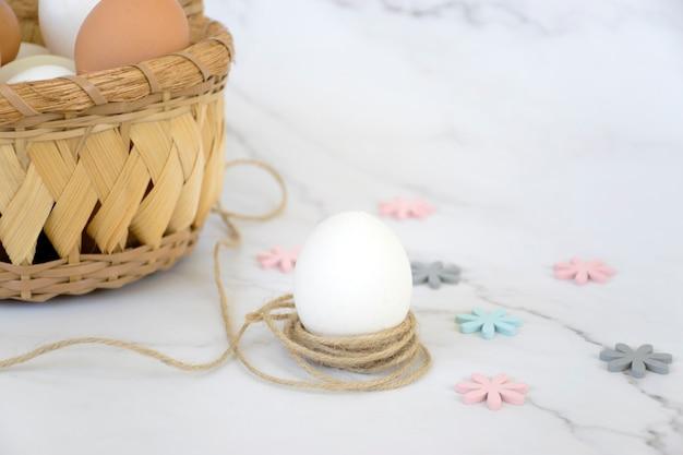 Wiklinowy kosz z jajkami i pojedynczym białym jajkiem w sznurze z kolorowymi kwiatami na marmurowym tle. wesołych świąt wielkanocnych.