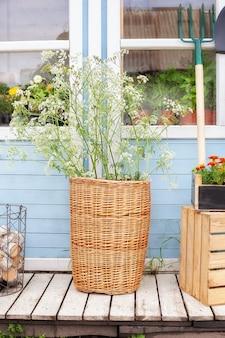 Wiklinowy kosz z kwiatami obok narzędzi ogrodowych na ścianie wiejskiego domu przytulny letni wystrój werandy dom