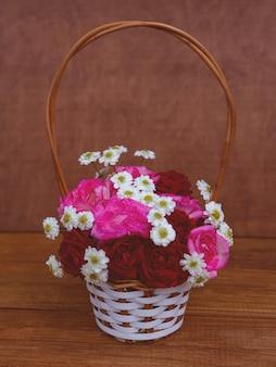Wiklinowy kosz z kwiatami, różami i stokrotkami