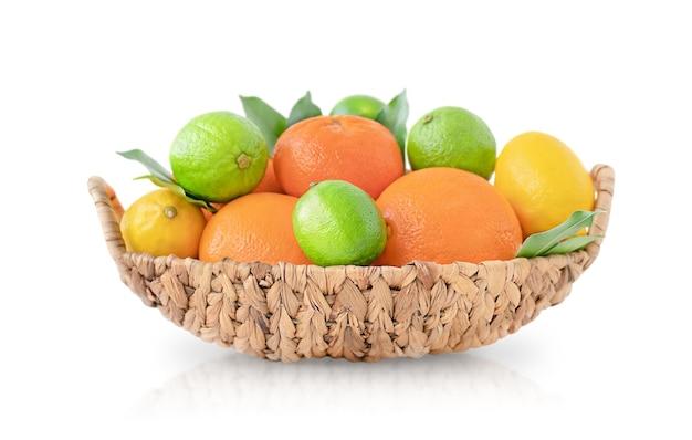 Wiklinowy kosz z owocami cytrusowymi na białym tle na białej powierzchni